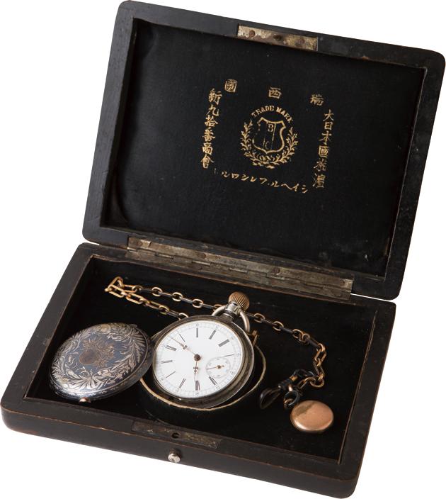 明治40年に販売した懐中時計と保証書。時計のデザインやカバーに施された意匠に当時のモダンさが垣間見える