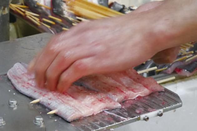 戸村さんのさばいた鰻をもうひとりの板前さんが手早く串刺しに。鮮やかな連係プレーで次々と串刺しができていく