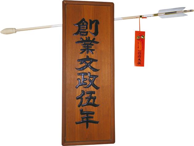 創業年を示す木製看板には魔よけの破魔矢が