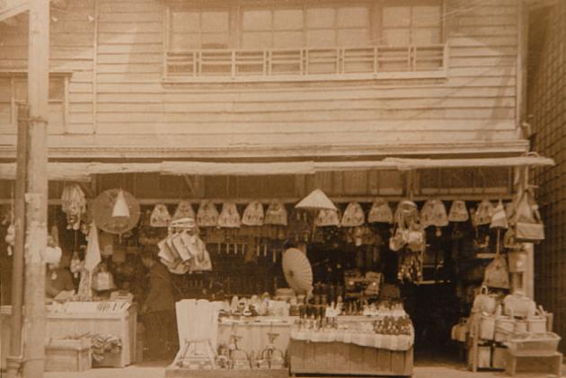 戦後の「コミナト」の写真。店先に、バスケットや笠などがずらりと並べられているのが見て取れる