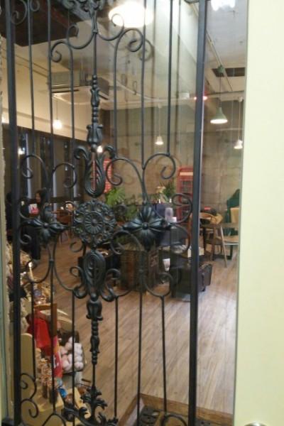装飾付きの鉄柵ドアがお洒落。ドア横のショップ看板にもこだわりを感じる