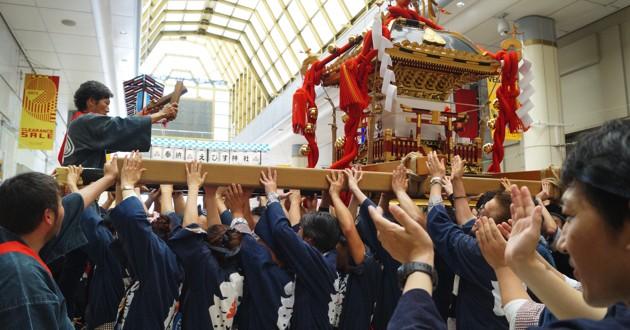 """拍子木を手に、神輿を統率する山田さん。担ぎ手が一斉に神輿を持ち上げる""""差し""""では担ぎ手の一体感が感じられる"""