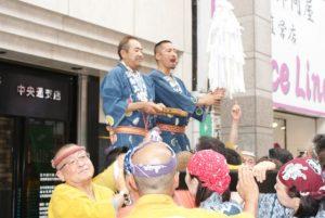 拍子木で御輿を制御する木村さんと岩本さん