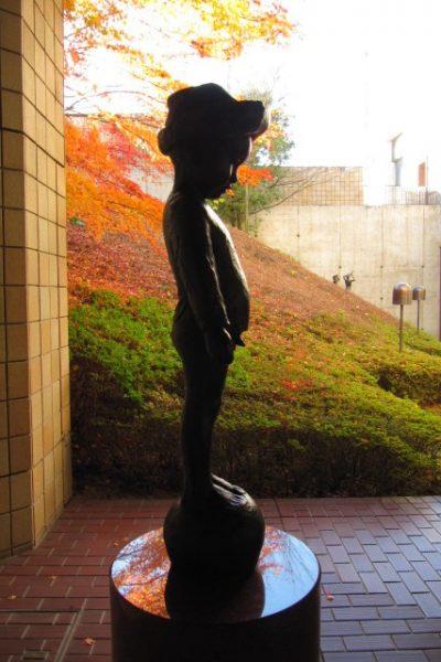 紅葉の秋の景色に佇む、佐藤忠良作「二歳(大)」
